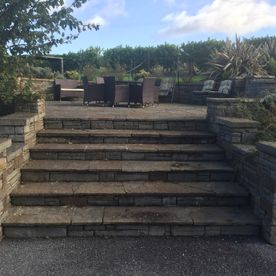 Random flagstone steps and patio complimented by grey sandstone