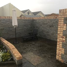 Grey sandstone paving enhanced with grey sandstone walling