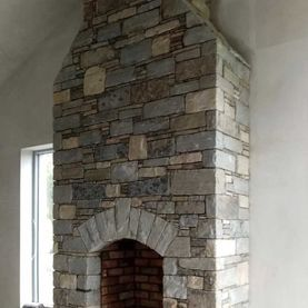 Mixed sandstone internal fireplace with handcrafted grey sandstone arch