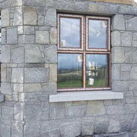 Grey granite laid in courses complimented with grey granite window cills