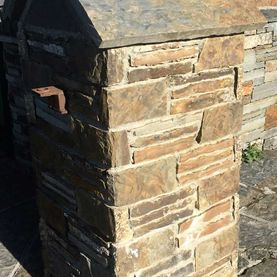 Split brown sandstone enhanced by grey sandstone paving