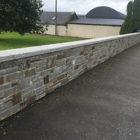 Dressed grey sandstone wall capping complimenting retaining wall